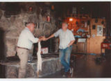 Photo of Willy Burgdorfer with another man standing before a stone fireplace holding a tick...