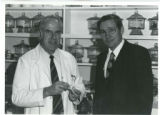 Photo of Willy Burgdorfer with a man in glasses in front of shelf of glass containers