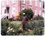 Man in overalls standing in rose garden, looking northwest
