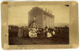Territorial Statehouse used as schoolhouse in 1870s. Class is posed to the northwest of the...