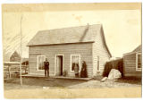 Family of four standing in front of pioneer home. Barn and part of another building in background