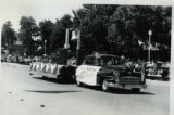 Parade with automobile and float from West Millard, Fillmore's Utah Centennial Celebration,...